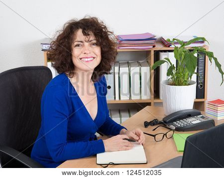 Smiling Business Woman With Notebook In The Office