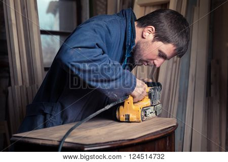 Portrait of Carpenter restoring old wooden furniture with belt sander in his Wood Shop poster