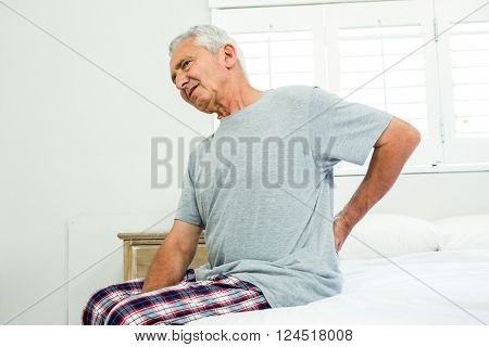 Senior man suffering from backache against window on bed at home