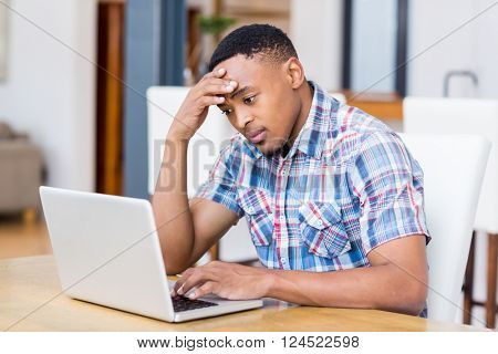 Tense young man using laptop in kitchen at home