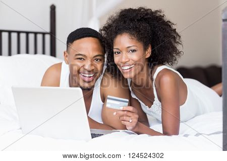 Happy couple shopping online through laptop using credit card in bedroom