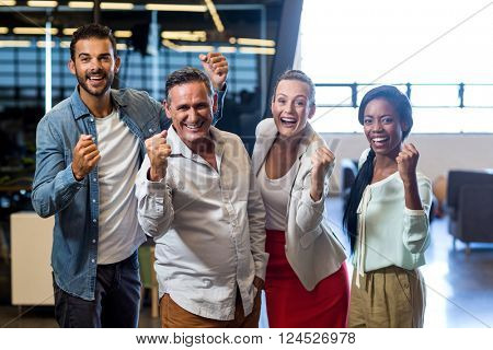 Portrait of business colleagues cheering with clenched fist in the office