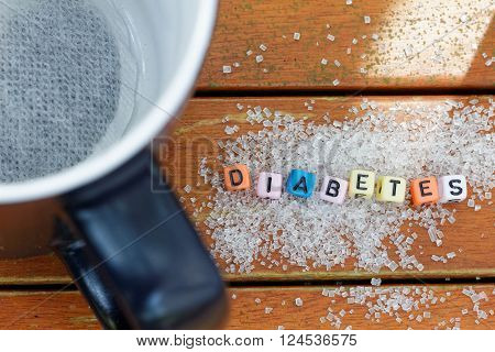 Black mug and scattered refined sugar on wooden table. poster