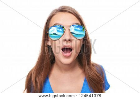 Holidays, travel, vacation concept. Surprised woman in sunglasses with tropical resort beach reflection with opened mouth