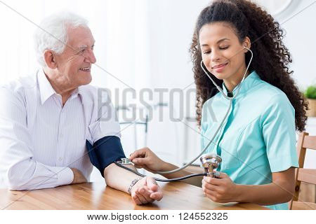 Professional Nurse Checking Patient's Blood Pressure
