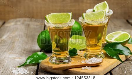 Still life, food and drink, holidays concept. Gold mexican tequila shot with lime and salt on a rustic wooden table. Selective focus
