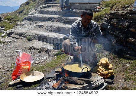 Shimla-Apr 24: A man preparing halwa poori(puri) outdoors during tonsure(mundan) ceremony, Shimla Apr 24, 2014 in Himachal Pradesh, India, Asia.