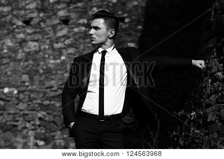 Man half face young handsome elegant model in unbutton suit with skinny necktie poses with hand in trouser pocket holds arm sideward outdoor black and white on masonry background