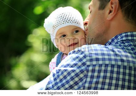 Father kissing and holding small daughter baby girl cute hazel-eyed kid tiny little child wearing white flower beanie hat outdoor on sunny summer day on blurred green background horizontal picture