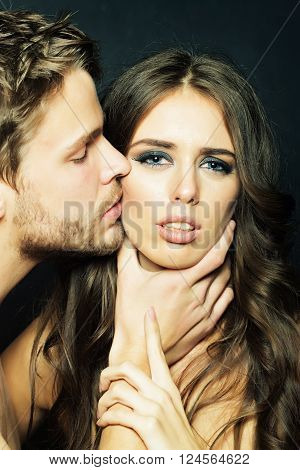 Closeup portrait of young attractive adult sexy couple of handsome man holding hand on neck of sensual brunette woman with long hair in studio on black backdrop vertical picture