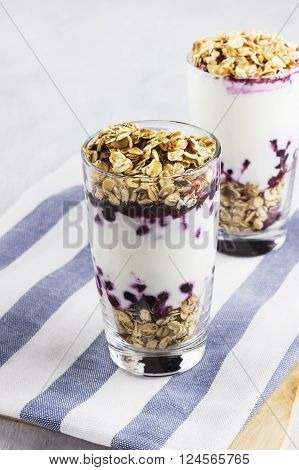 Useful Dessert Of Granola, Yogurt And Blueberry In Glass On A White Background