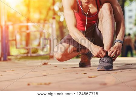 Cropped image of jogger tying shoe laces before jogging