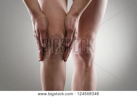 Female's healthy legs. Woman touching her injured knee. Rheumatism or arthritis concept.