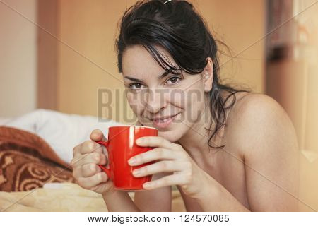 Woman in morning lie and holding cup of coffee, nice natural light and worm color