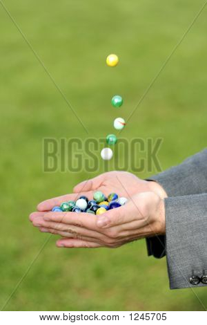 Marbles Dropping Into A Hand Outdoors