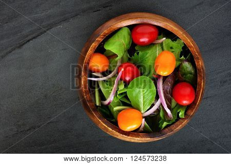Garden Salad With Cherry Tomatoes And Red Onions In Wooden Bowl Overhead View On Dark Slate Backgrou