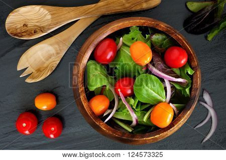 Mixed Salad With Cherry Tomatoes And Red Onions In Wooden Bowl, Overhead Scene On Slate Background