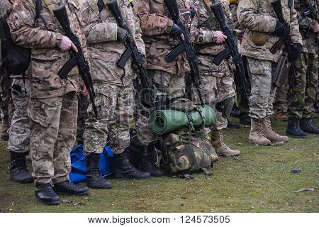 Army parade - soldiers in uniform with assault rifles in handsin rest position standing poster