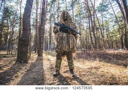 Sniper in camouflaged ghillie suit standing in forest with rifle in hands.Low angle view.Selective focus.