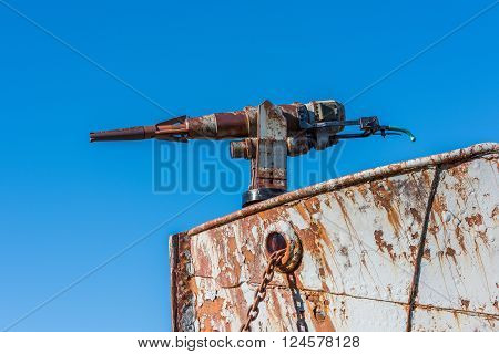 Close-up of rusty harpoon gun in bows