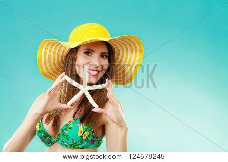 Woman In Yellow Hat Holding White Shell