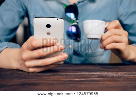 Young Woman In A Denim Jacket Sits At A Table And Holding A Mobile Phone And A Cup Of Coffee
