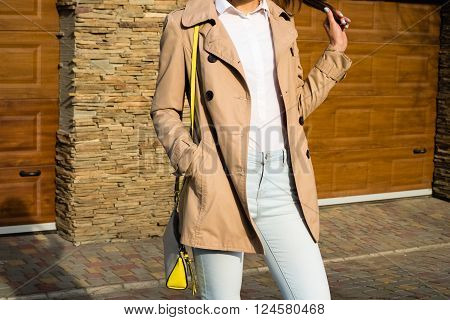 Slim Girl In A Beige Coat, Blue Jeans And White Shirt Outdoors