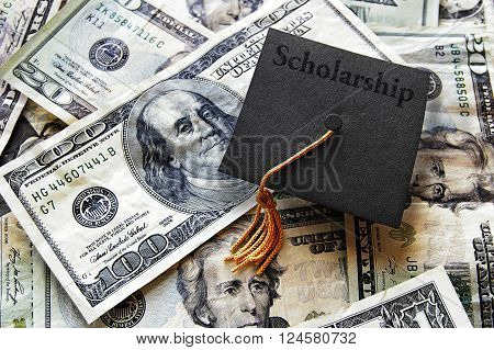 Miniature graduation cap with Scholarship text on hundred dollar bills