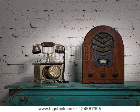 Still life of retro old wooden radio and old telephone set on a green vintage wooden stained table and background of white painted bricks wall