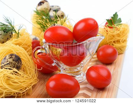 Glass Gravy boat with cherry tomatoes. On a white background.