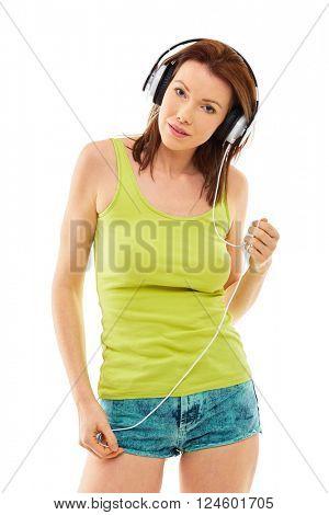 Girl in summer shorts listen to music on her headphones, isolated over white background