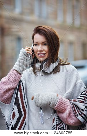 Young woman talk over her mobile while walking down the street