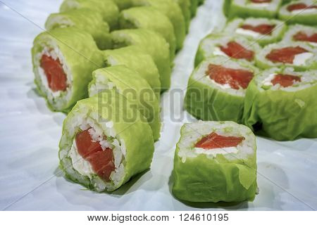 Sliced green salmon sushi on a plate. Cabbage leaves were used to wrap the rolls instead of dried seaweed lavers.