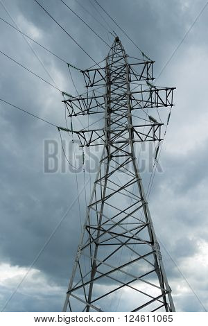 Electric pole power lines and wires on storm omnious sky. High voltage electricity pylons against rainy cloud.