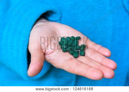 spirulina tablets in the palm of a woman's hands