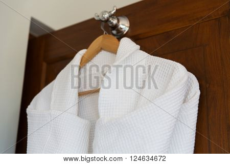 bath, clothes, hygiene and luxury concept - close up of two white bathrobes hanging on wooden hanger at home or hotel