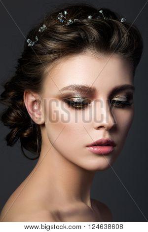 Portrait of young beautiful woman with bridal makeup and coiffure. Modern smokey eyes make up. Studio shot. Salon make-up
