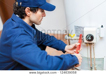 Plumber fixing an hot-water heater poster