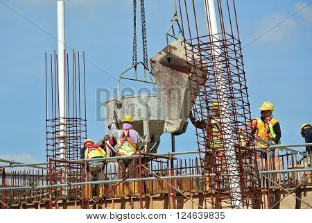 SELANGOR, MALAYSIA - DECEMBER 12, 2015: A group of construction workers pouring wet concrete using concrete bucket into the timber form work at the construction site.