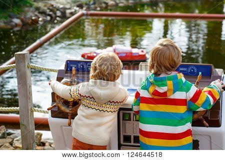 Two little kids playing with radio controlled boats or ships in park on warm and sunny summer day. Active leisure for children. Boys having fun together outdoors.