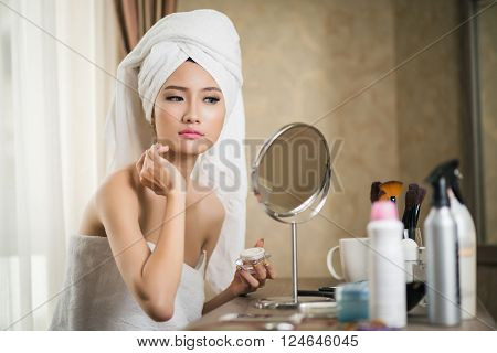 Flawless young woman applying moisturizer in front of mirror
