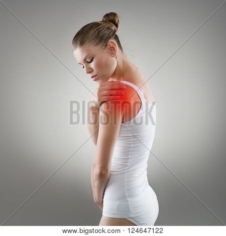 Young woman having pain in shoulder. Joint illness and treatment