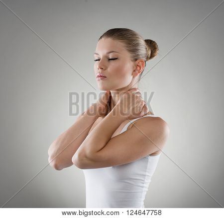 Close-up portrait of young Caucasian woman massaging her painful nape. Neck and back stretch concept.