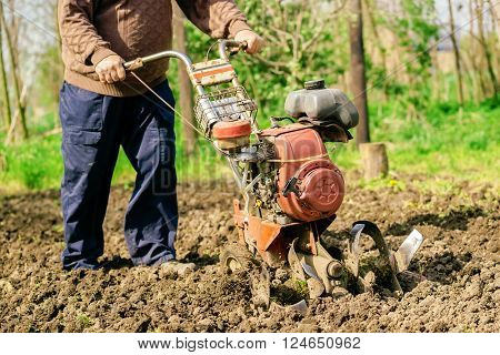 Man preparing garden soil with cultivator tiller new seeding season on home vegetable farm