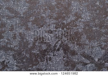 texture of textile fabric with spots from glossy scaly leather of dark color for an abstract background or for the textured wallpaper