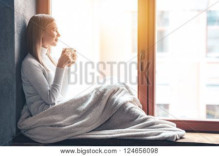So nice to spend a day at home! Side view of beautiful young woman holding coffee cup and looking through window while sitting at windowsill at home
