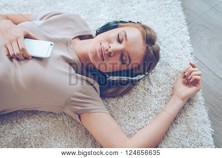 Feeling calm. Top view of beautiful young woman listening to music and keeping eyes closed while lying on carpet at home