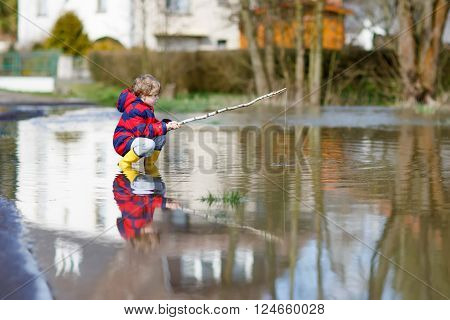 Funny little kid boy in rain boots playing with selfmade fishing rod by a puddle on warm spring day. Active leisure for children. Child having fun outdoors.