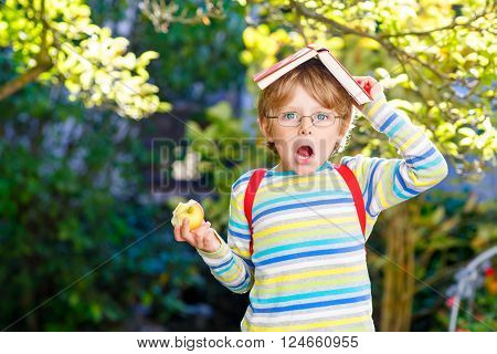 Confused little kid boy with glasses, books, apple and backpack on his first day to school or nursery. Child outdoors on warm sunny day, Back to school concept