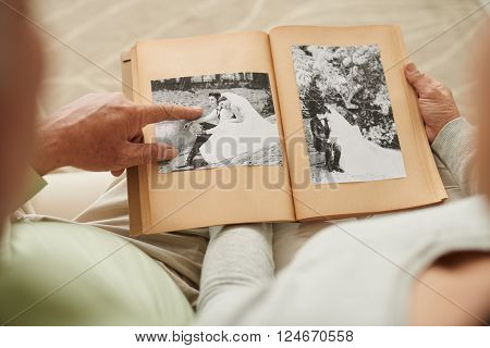 Senior couple at their wedding photos in photo album